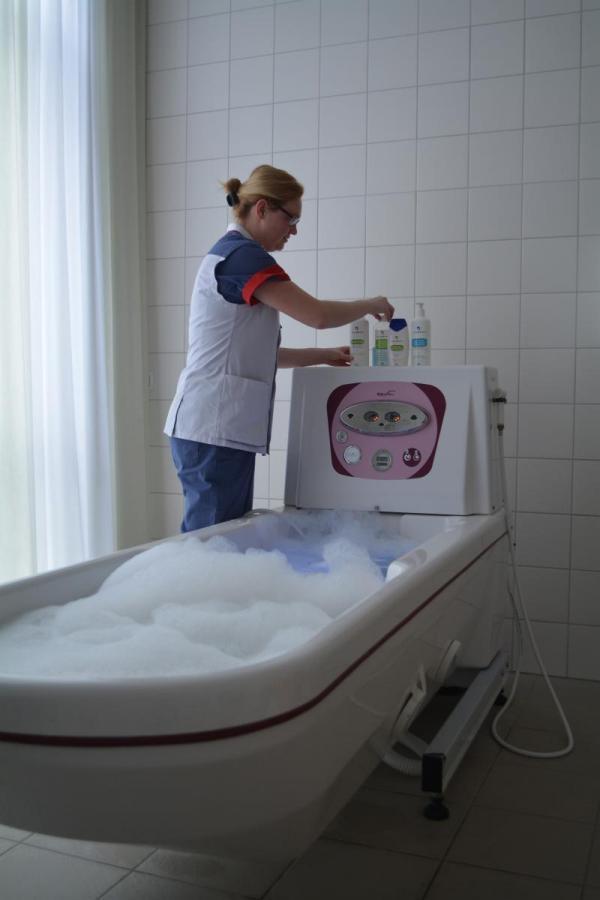 Verzorgende bereidt een schuimend bad voor