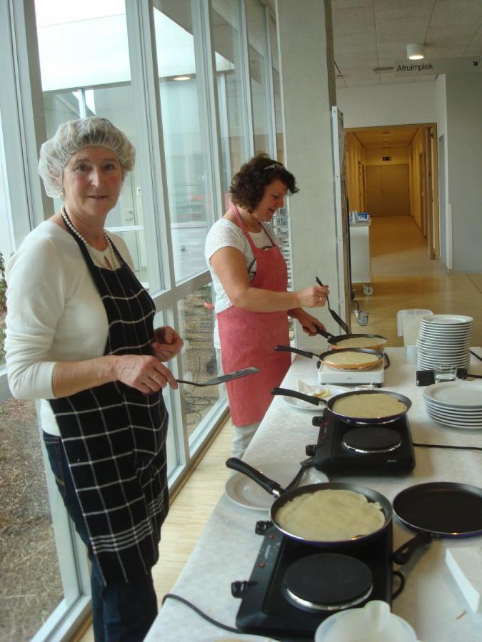Twee vrijwilligsters kookteam bakken pannenkoeken.