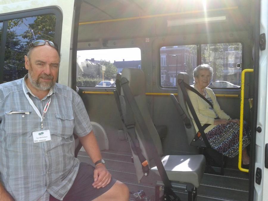 Vrijwillige chauffeur houdt schuifdeur handicar open