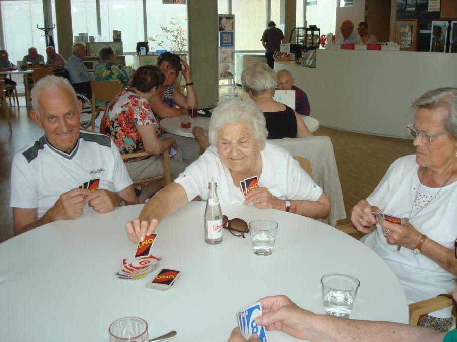 Vrouw neemt speelkaart van tafel. Medespelers kijken toe.