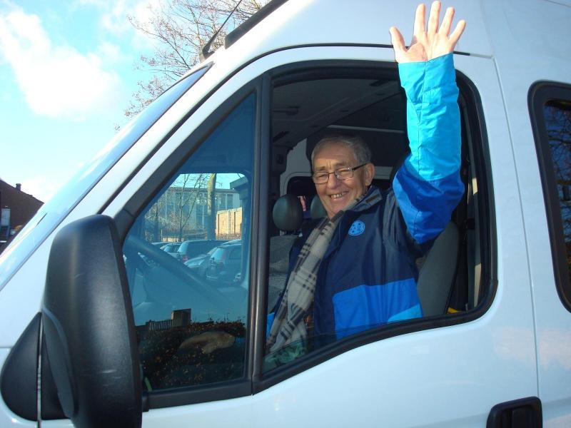 Vrijwillige chauffeur zwaait door raam handicar