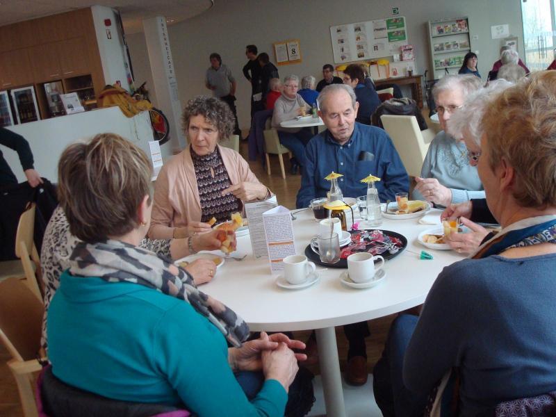 Zes mensen genieten van een drankje aan een ronde tafel in de cafetaria van het dienstencentrum