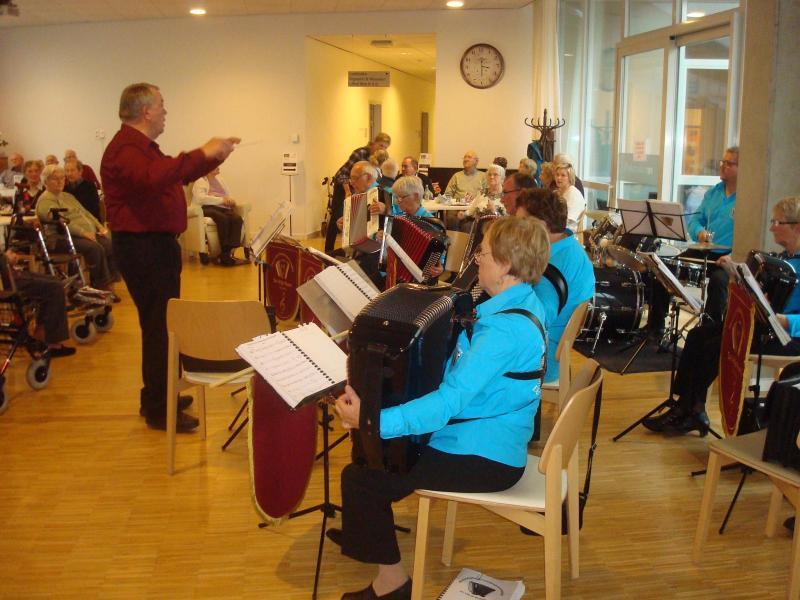 Dirigent zwaait de maat voor groep accordeonspelers