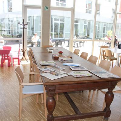 Grote tafel met tijdschriften en kranten in de cafetaria