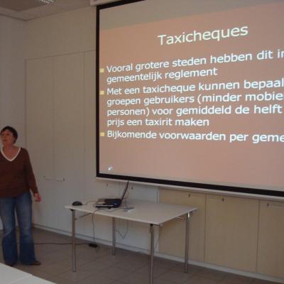 Vrouw geeft uitleg, rechtstaande voor een projectiescherm