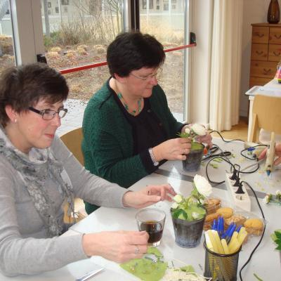 Twee leden van het decoteam maken een bloemstukje als tafelversiering