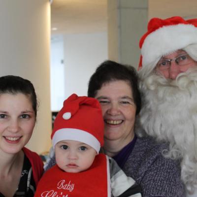 De kerstman poseert met drie bezoekers in de cafetaria