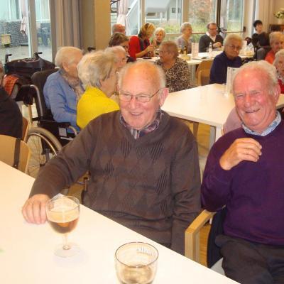 Twee lachende mannen bij een glas abdijbier