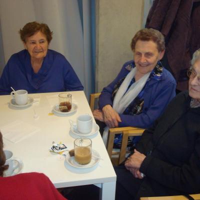 Drie vrouwen aan tafel bij een tas koffie