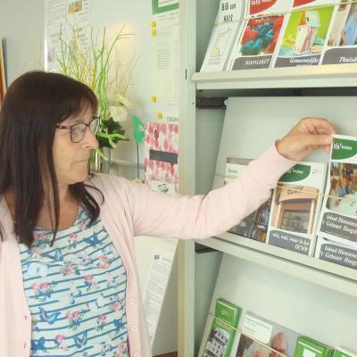 Bezoeker dienstencentrum neemt wegwijsfolder uit folderrek